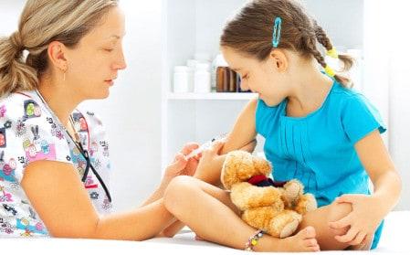 enfermera con uniforme estampado pinchando niña